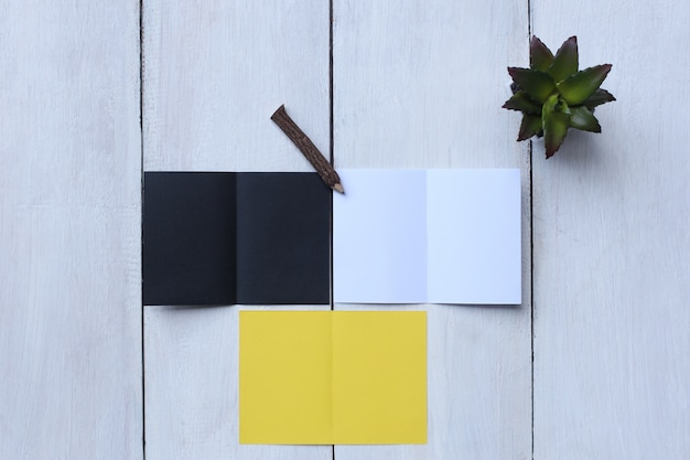 Papel de vista superior amarelo, papel branco, papel preto, lápis e vaso de flores no chão de madeira branco