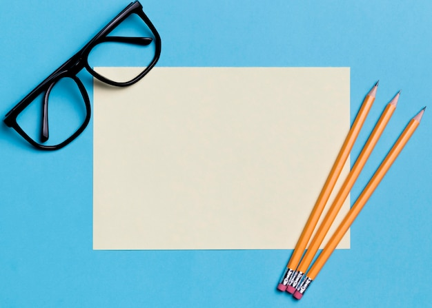 Papel de vista superior e óculos com lápis