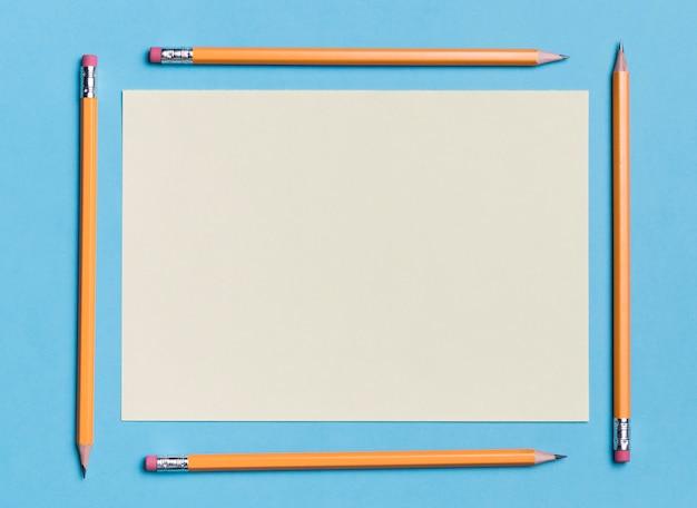 Papel de vista superior, rodeado por lápis em cima da mesa