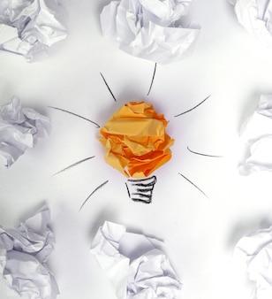 Papel desperdiçado no chão com lâmpada de ideia