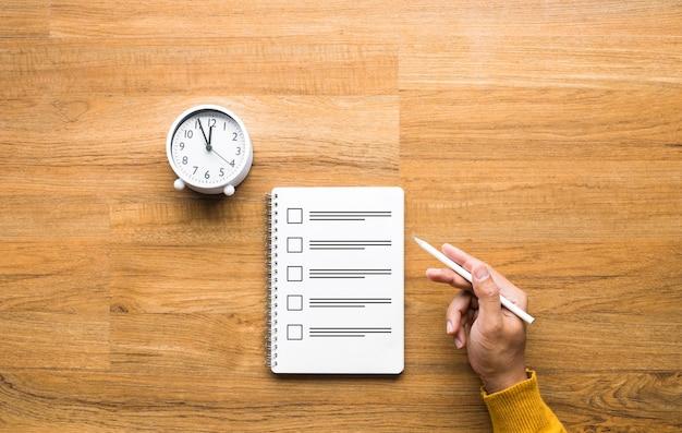 Papel do exame e um relógio em uma mesa de madeira