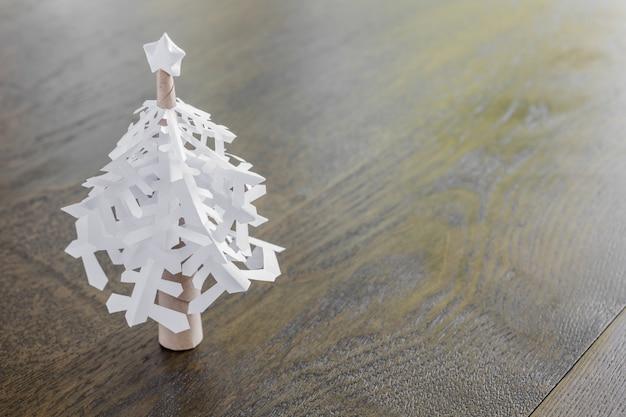 Papel dos flocos de neve da árvore de natal na tabela de madeira
