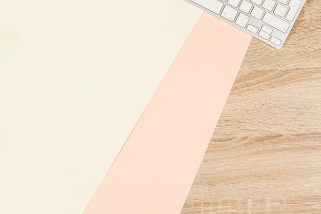 Papel duplo em branco e teclado na mesa de madeira