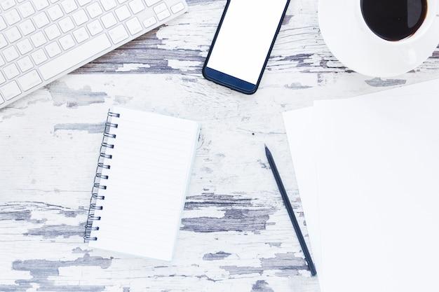 Papel e caderno perto de dispositivos eletrônicos e xícara de café