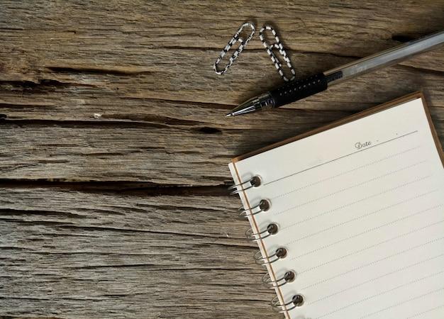 Papel e caneta na velha mesa de madeira