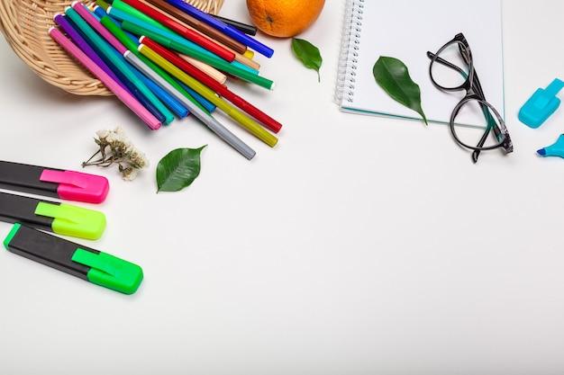 Papel e canetas de feltro coloridas na mesa branca