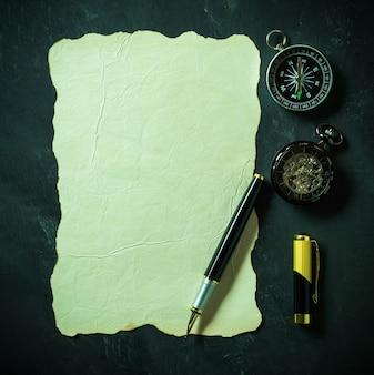 Papel e pena do vintage com compasso e relógio de bolso no fundo preto.