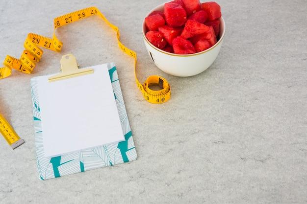 Papel em branco anexado na prancheta com fita métrica e cubos de melancia na tigela