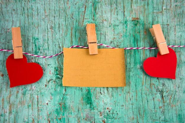 Papel em branco antigo e corações vermelhos de papel penduraram em prendedores de roupa em uma corda