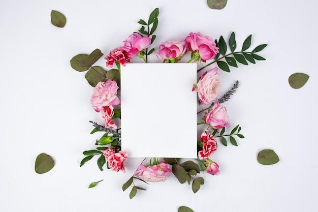 Papel em branco branco em lindas flores sobre o pano de fundo branco