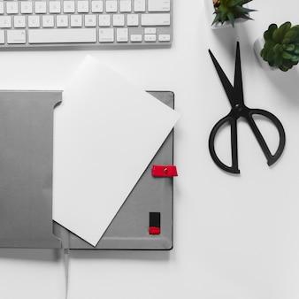 Papel em branco branco na bolsa com teclado e tesoura em fundo branco