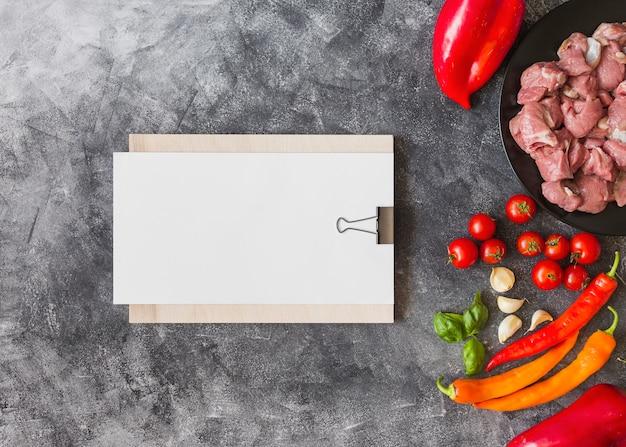 Papel em branco branco na prancheta com ingredientes para fazer carne no pano de fundo texturizado
