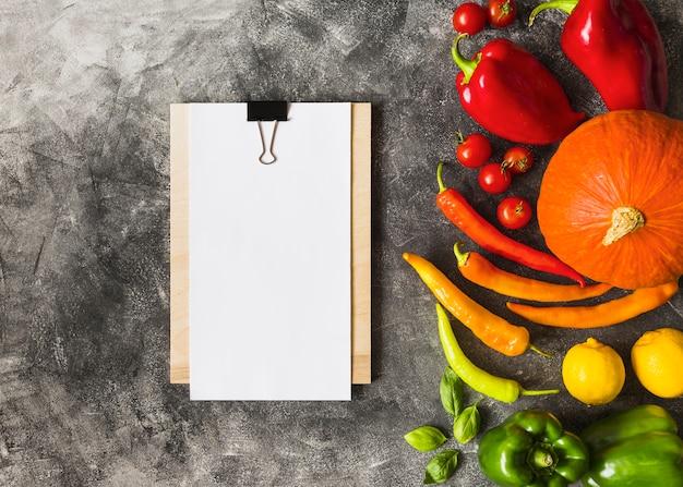 Papel em branco branco na prancheta com legumes maduros contra o fundo grunge
