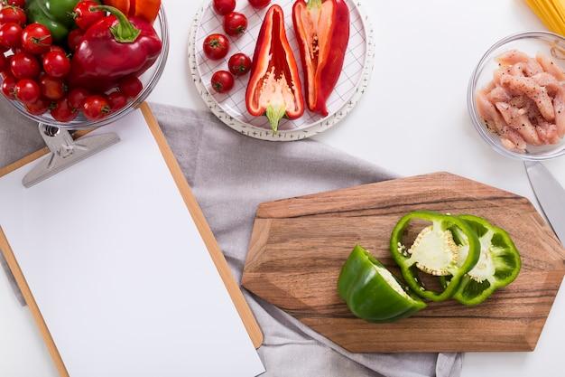 Papel em branco branco na prancheta com pimentão; tomate cereja e frango no pano de fundo branco