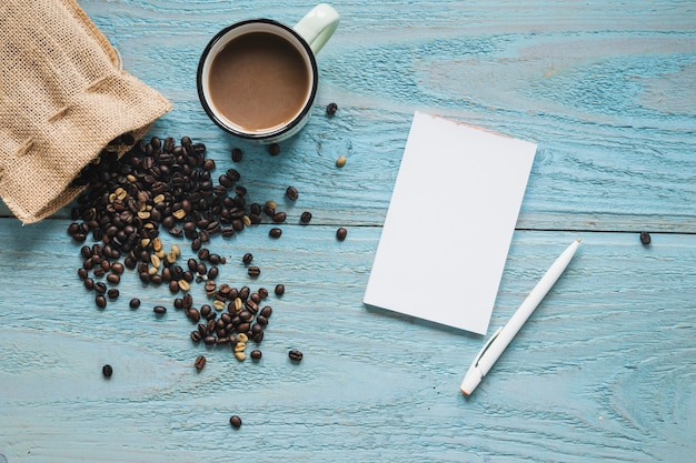 Papel em branco; caneta com xícara de café e grãos de café na mesa texturizada azul