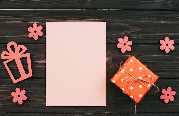 Papel em branco com caixa de presente na mesa