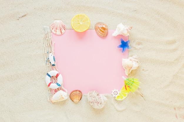 Papel em branco com conchas do mar na areia