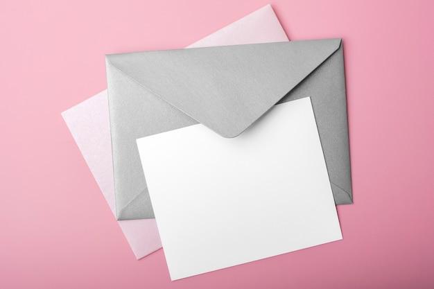 Papel em branco com envelopes em fundo rosa. cartão vazio para seu projeto, mock up