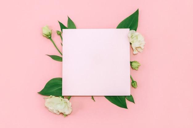 Papel em branco com flores brancas frescas em rosa pastel