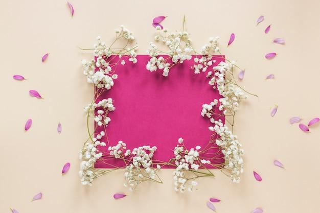 Papel em branco com galhos de flores na mesa de luz