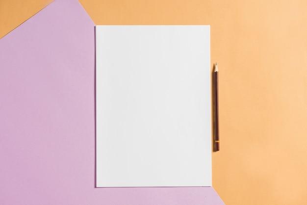 Papel em branco com lápis em papéis de cartão colorido
