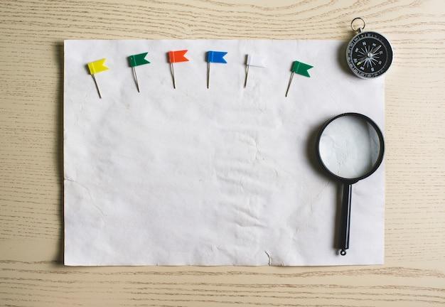 Papel em branco com ponteiros coloridos, compasso e lupa