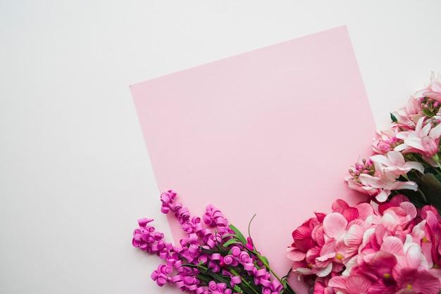 Papel em branco-de-rosa com flores coloridas em fundo branco