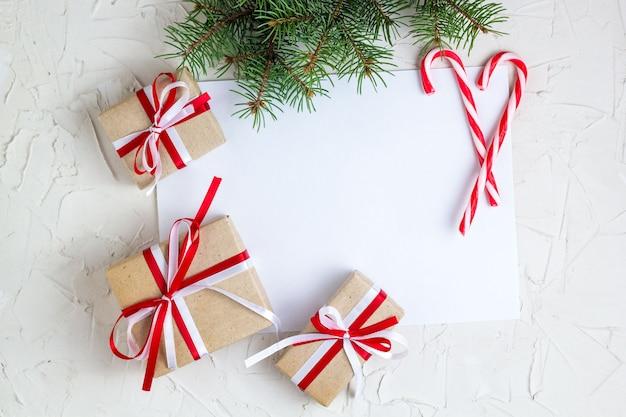 Papel em branco deitado com pirulito, galhos de árvores de natal e presentes