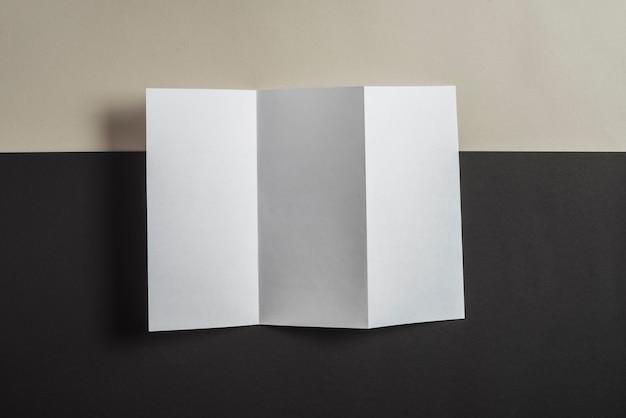 Papel em branco dobrado no pano de fundo