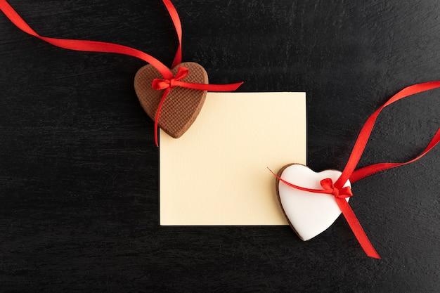 Papel em branco e dois biscoitos de coração de gengibre. espaço para suas saudações.