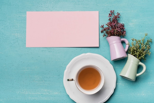 Papel em branco e vasos com uma xícara de chá no plano de fundo texturizado azul