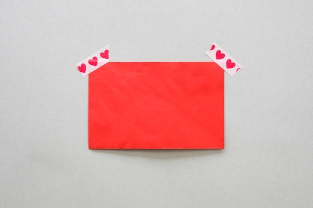 Papel em branco fixado com fita adesiva com corações