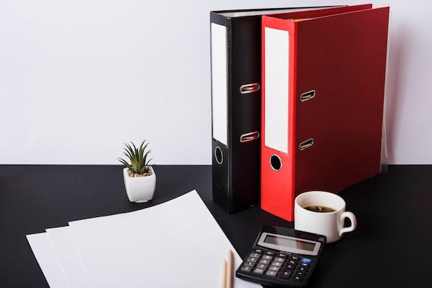 Papel em branco; lápis; calculadora; xícara de café e arquivos na mesa preta