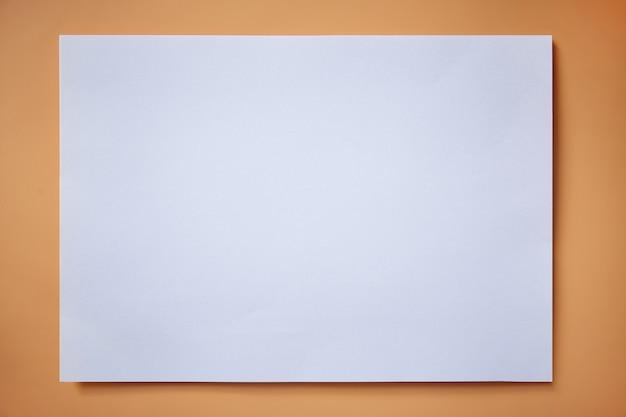 Papel em branco maquete branco sobre um fundo laranja. copie o espaço para o texto.