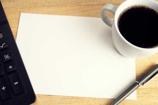 Papel em branco na mesa de mesa de madeira com uma xícara de café e calculadora. modelo de simulação. conceito de economia, financeiro ou de negócios