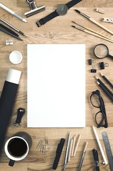 Papel em branco na mesa do artista com material de escritório, maquete