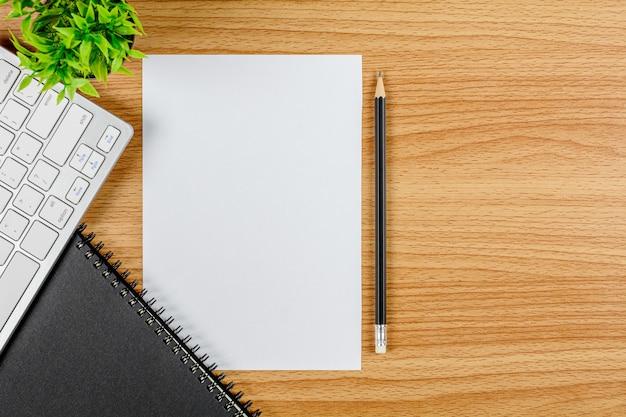 Papel em branco nota com um teclado de computador, caneta e um notebook na mesa de escritório de madeira