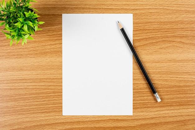 Papel em branco nota e um lápis na mesa de madeira