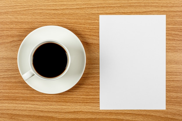 Papel em branco nota e uma xícara de café branco na mesa de madeira