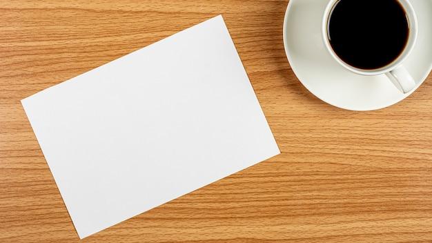 Papel em branco nota e uma xícara de café na mesa de madeira