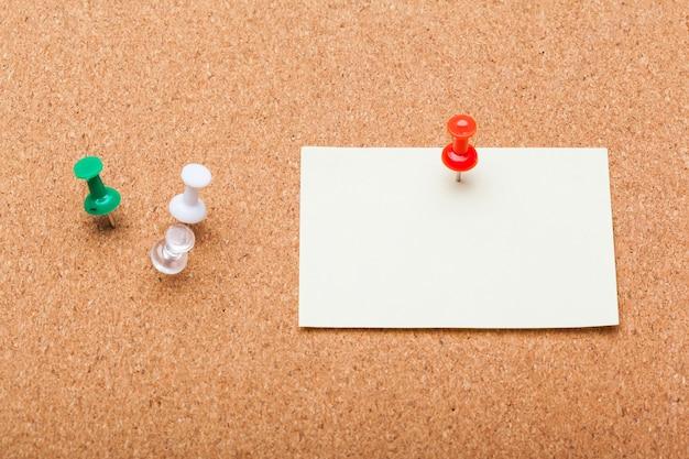 Papel em branco nota em uma placa de cortiça