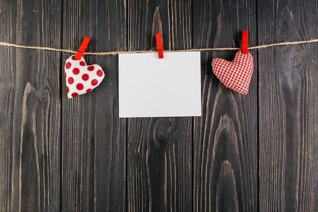 Papel em branco pendurado entre corações na corda