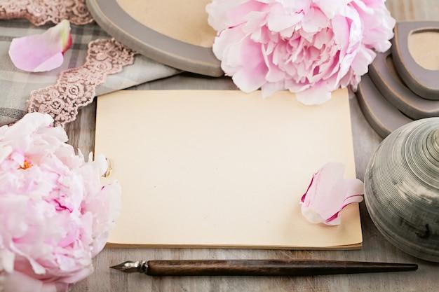 Papel em branco vazio sobre fundo retrô com flores de peônia e renda e caneta vintage