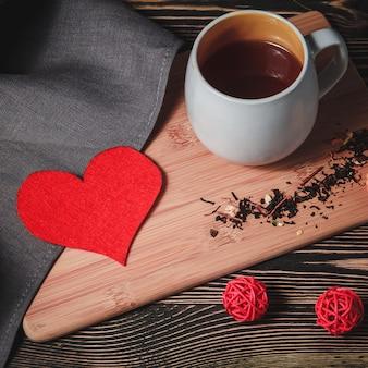 Papel em forma de coração vermelho com uma xícara de chocolate