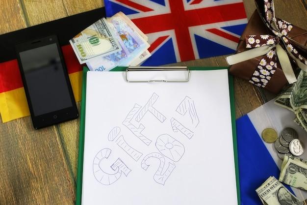 Papel forma uma textura em uma mesa de madeira com caixas de presente embaladas, telefones celulares e bandeiras