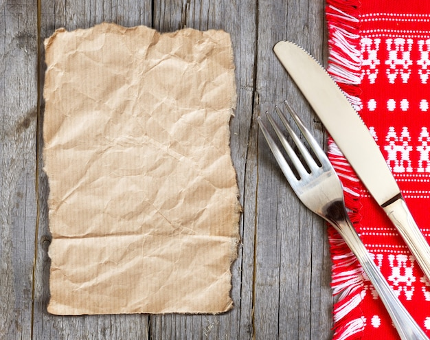 Papel, garfo e faca na toalha de cozinha em uma vista de mesa de madeira com espaço de cópia em papel artesanal
