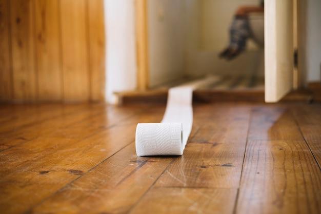 Papel higiênico branco no piso de madeira