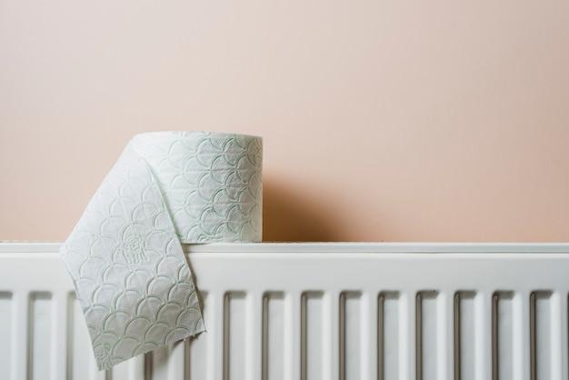 Papel higiênico branco no radiador contra a parede