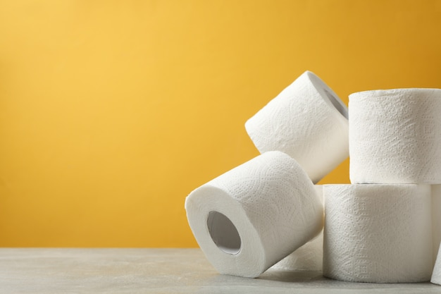 Papel higiênico contra mesa amarela