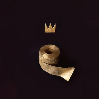 Papel higiênico de ouro com uma coroa em uma parede preta
